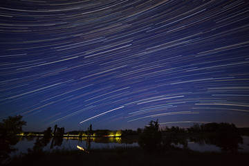 Star trails in the night sky. A view of the starry space in the background of the river.
