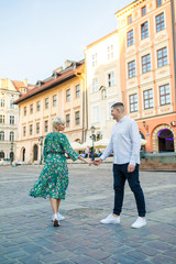 young beautiful couple of tourists stand in the square in the city of Krakow in Poland