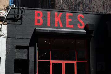 Exterior of a generic bike shop in New York. Bikes painted in red on black brick building. Generic bicycle storefront painted red and black. Facade of a bike store in an urban area, USA.