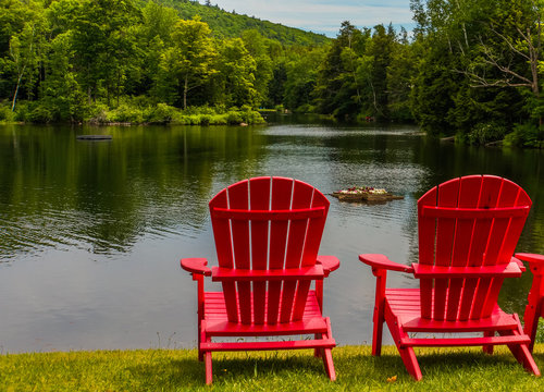 two bright red Adirondack chairs on the shoreline of lake in summer with a floating flower box with flowers blooming