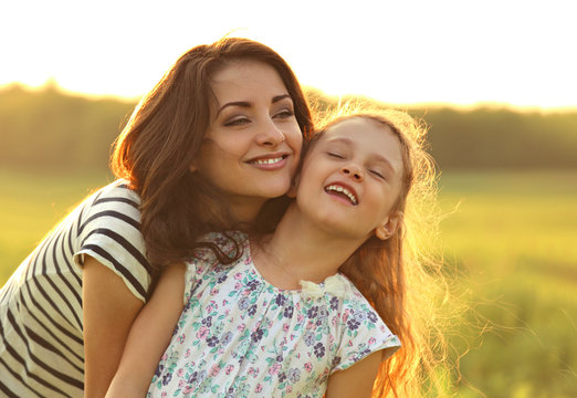 Emotional calm mother hugging her laughing kid girl with loving eyes on sunset bright summer background. Closeup bright color portrait