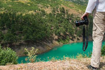 Photographer with DSLR camera in mountains