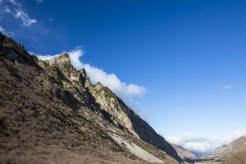 Горный пейзаж. Вершины в белых облаках, Красивый вид на живописное ущелье, панорама с высокими горами. Природа Северного Кавказа, отдых в горах