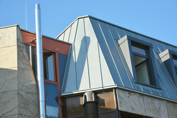 Modernes Stehfalz-Metalldach mit Dachfenster, Dachrinne und Edelstahl-Schornstein