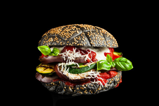 Black burger with Italian stuffing of Parmigiana from eggplants, zucchini and tomato sauce. Ideal Italian option for a snack, lunch or light dinner. Vegan and Vegetarian Healthy Eating