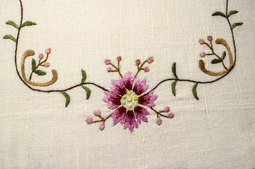 Part of the embroidered corner from the border with a pinkish-red flower and buds on wavy branches with small leaves