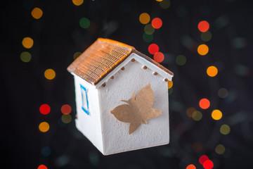 Butterfly on a Model house on a bokeh light