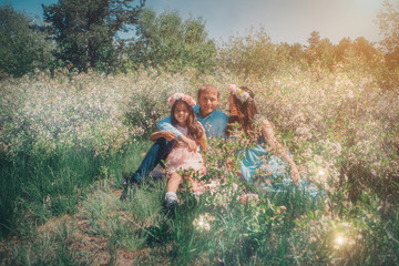 man, pregnant woman and little girl: family photo outdoors