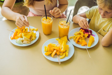 Mom and son are eating fruits and juice in a cafe