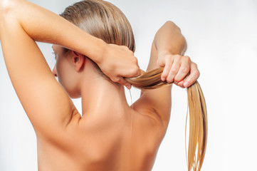 Blond woman with long wet hair is applying hair conditioner