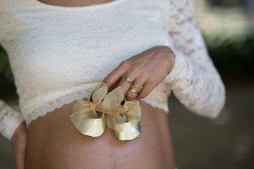 Detail of pregnant woman holding golden girl shoes on belly