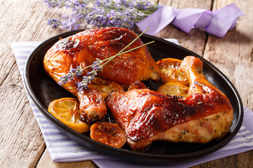 Delicious food: grilled glazed chicken legs with lavender honey and lemon close-up on a plate. horizontal