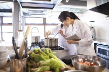 注意深く鍋の中を覗く栄養士たち