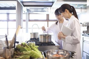 鍋で調理をしている栄養士たち