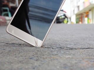 Smartphones drop to the ground. Make the screen broken and damaged.Background image blur With the concept of accident insurance technology, repair and maintenance. Event over expected data retention.