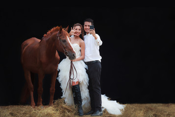 Young newlywed couple, handsome groom and beautiful beauty bride in fashionable white bridal wedding dress selfie using smartphone with horse on black  background