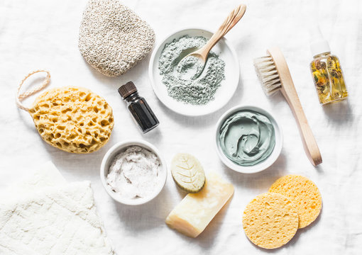 Spa accessories - nut scrub, sponge, facial brush, natural soap, clay face mask, pumice stone, essential oil on a light background, top view. Healthy lifestyle concept. Beauty, skin care. flat lay