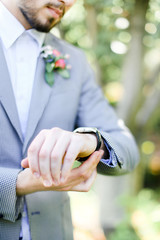 Caucasian groom with beard looking at watch and wearing grey suit. Concept of wedding day and time.