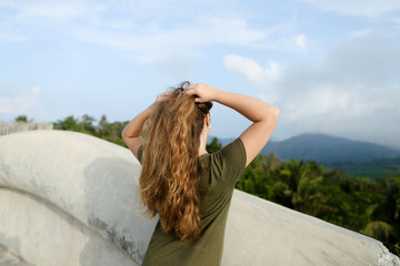 Young woman with long hair looking at mountains and wearing khaki dress. Concept of nature and relaxing.