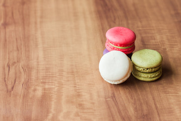 Colorful French Macarons on wooden background.