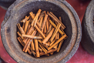 Cinnamon sticks in a pot against the background of other spices