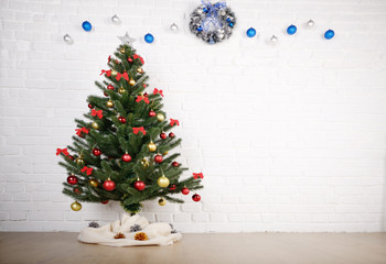 Blue and silver balls and wreath on white brick wall holiday background with christmas tree