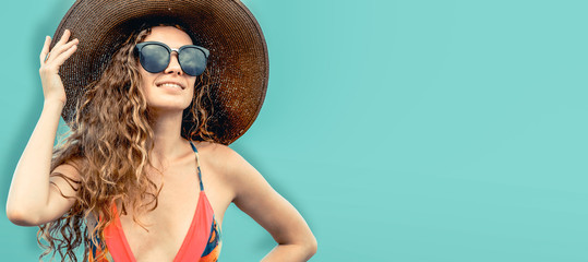 Woman in swimsuit posing on color background.