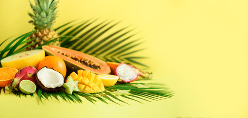 Assortment of exotic fruits on yellow background. Banner. Detox, vegan food, summer concept. Papaya, mango, pineapple, carambola, dragon fruit, kiwi, orange, melon, coconut, lime over palm leaves.