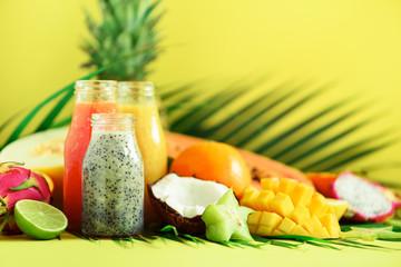 Juicy papaya and pineapple, mango, orange fruit smoothie in jars on yellow background. Detox, summer diet food, vegan concept. Copy space. Fresh juice in glass bottles over palm leaves.