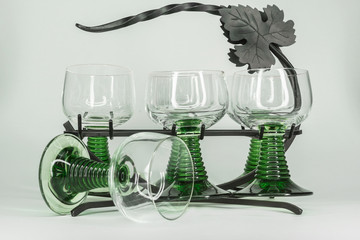 Six Wine Glasses With Green Stems sitting in a wrought iron rack with a wine leaf