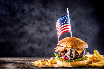 Close-up home made beef burger with american flag and fries on wooden table