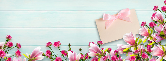 Magnolia flowers and roses on background of shabby wooden planks  and congratulatory card with bow
