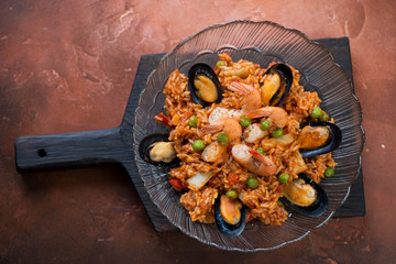 Plate of seafood paella on a black wooden serving board, above view over fire warm rusty metal background