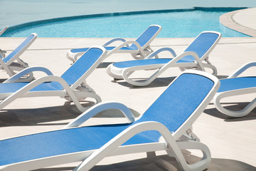 Many blue chaise lounge by the pool.