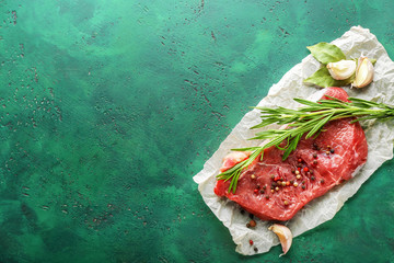 Fresh raw meat with spices and rosemary on color background