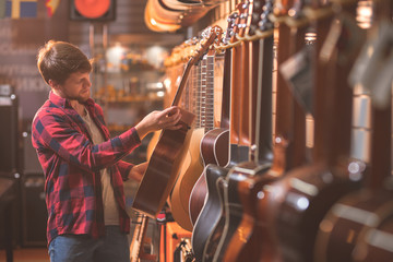 Photo sur Toile Magasin de musique A young man choosing a guitar