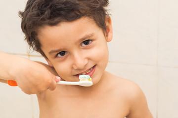 brown-eyed boy brushing his teeth in the bathroom