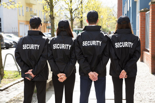Rear View Of Security Guards Standing In A Row