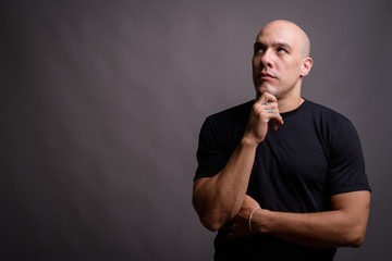 Handsome bald man against gray background