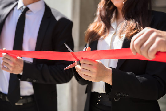 Businesspeople Hand Cutting Red Ribbon