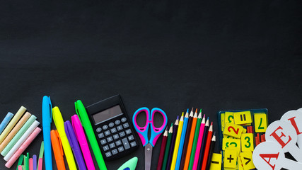 School supplies mockup on blackboard background with copyspace. Bright multicolored, pencils, pens, scissors, notepads, letters, figures, brushes, paints, clamps, eraser and other stationery
