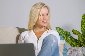 beautiful and happy elegant blond woman early 40s relaxed at home living room using internet on laptop computer working comfortable on sofa couch