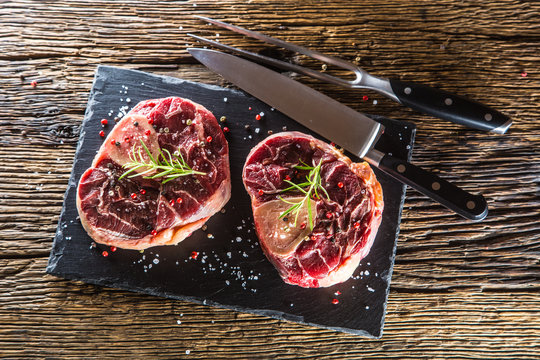 Two pieces raw beef shank on slate board and wooden table.