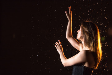 Girl in black dress, drops of water and dark background