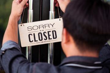 man hanging close signboard at the door of restaurant