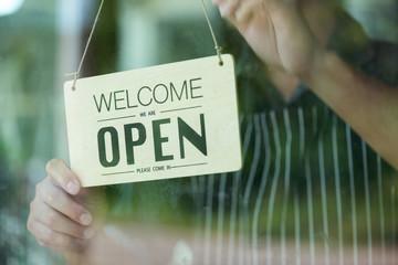 man hanging open signboard at the door of restaurant