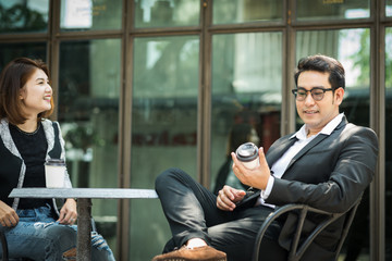 Asian businessman taking a break with coffee and talking with his partner outdoor.