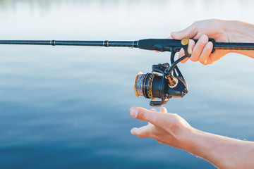 Fishing. A man in his hands holds a reel