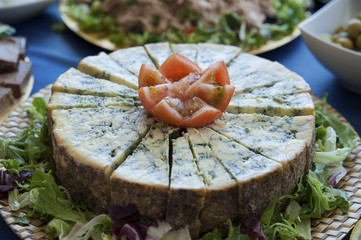 Aged blue cheese wheel, a popular fermented dairy, cut in small even triangles with tomato garnish, at a buffet restaurant, a party or a reception, served as a starter or as tapas