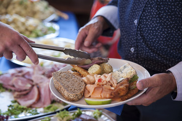 Male senior holding a plate with a selection of cold bits, bread and salad and being served a slice of meat at the buffet style dining